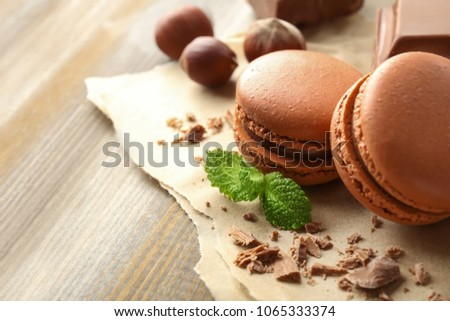 Tasty macarons, chocolate and hazelnuts on wooden background #1065333374