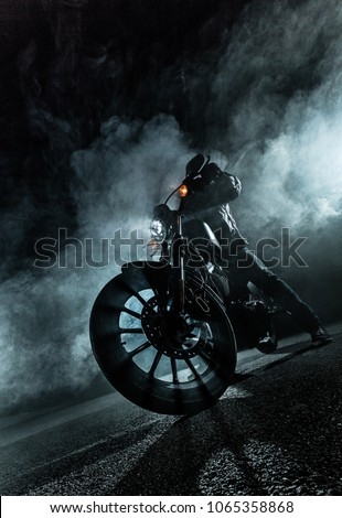 High power motorcycle chopper at night. Smoke effect on dark background. #1065358868