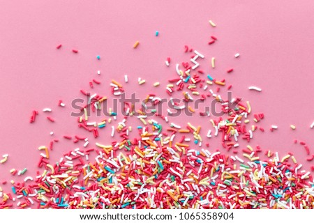 Colorful sprinkles on a pink background, top view with copy space Royalty-Free Stock Photo #1065358904