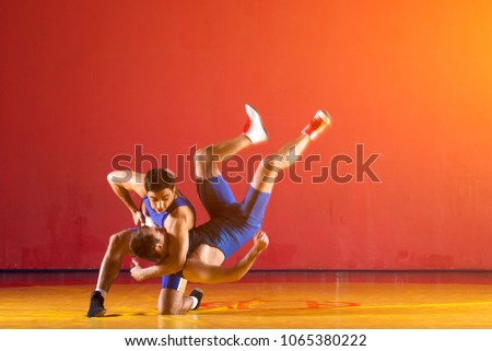 Two greco-roman  wrestlers in blue uniform wrestling   on a yellow wrestling carpet in the gym