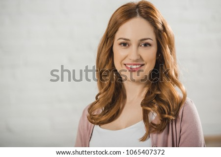 portrait of beautiful woman smiling at camera on grey #1065407372
