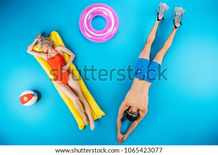 top view of young couple resting with beach items on blue, summer vacation concept #1065423077