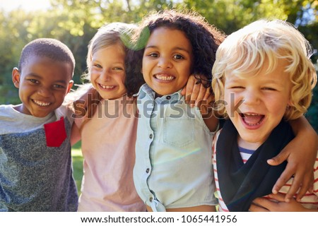 Four kids hanging out together in the garden Royalty-Free Stock Photo #1065441956