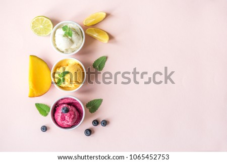 Three various fruit and berries ice creams on pink background, copy space. Frozen yogurt or ice cream with lemon, mango, blueberries - healthy summer dessert. #1065452753