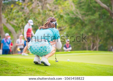 Golfer putting golf ball on green grass for check fairway to hole on golf course #1065458822