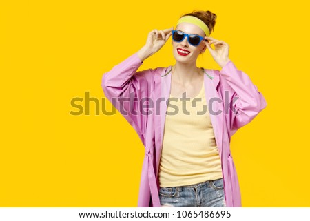 Young woman on a yellow background and pink coat and sunglasses. Colour obsession concept.  Minimalistic style. Stylish Trendy #1065486695