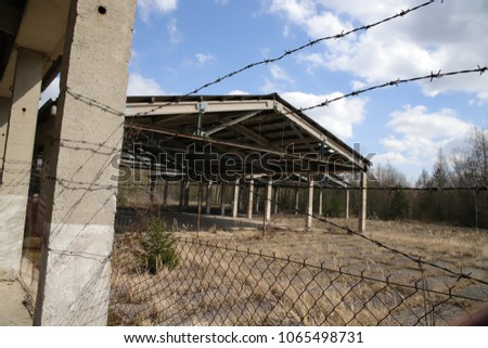 wired fence ruined house #1065498731