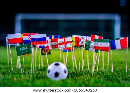 Football ball on green grass and all national flags  #1065543263