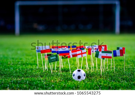 Football ball on green grass and all national flags  #1065543275