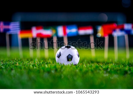 Football ball on green grass and all national flags  #1065543293