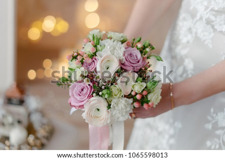 Luxurious bridal bouquet of light pink ranunculus, pink roses, eucalyptys berries and white david austin roses with lots of green leaves, with bright yellow bokeh lights on the background #1065598013