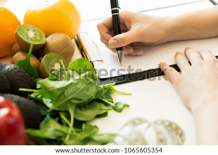 Nutritionist woman writing diet plan on table full of fruits and vegetables #1065605354