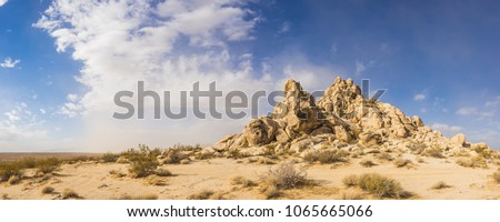 Sand desert holds pile of rock boulders forming a hill in the midst of the Mojave desert. #1065665066