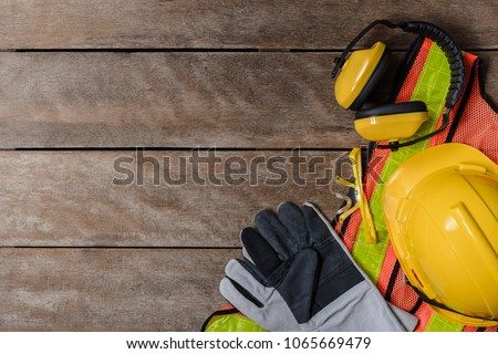 Standard construction safety equipment on old wooden background. top view, safety first concepts Royalty-Free Stock Photo #1065669479