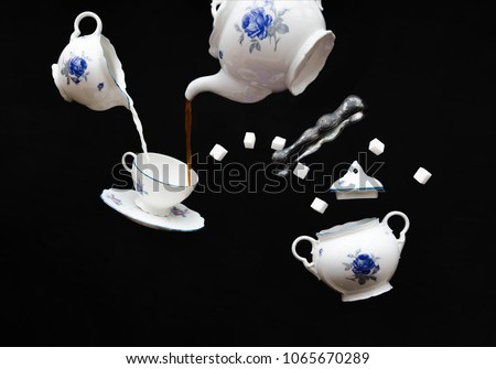 Haunted coffee party - flying porcelain coffee set on black background - ghost service