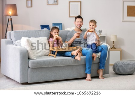 Father with children having breakfast on sofa at home #1065692216