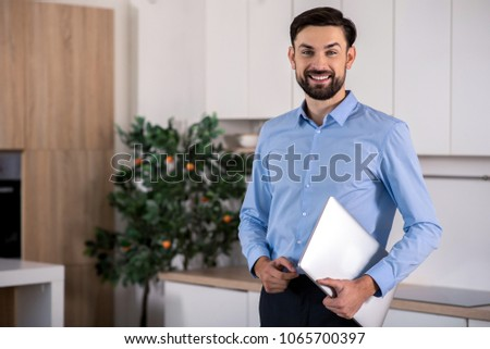 Working mood. Cheerful smiling businessman holding his laptop and standing in the kitchen #1065700397