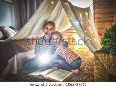 Two cute little children are reading a book with flashlights in tent. Happy girls playing at home. Funny lovely kids having fun in room.  #1065729065