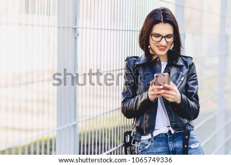 Woman in leather jacket in glasses messaging on phone and smiles at street #1065749336