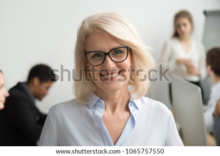 Portrait of smiling senior businesswoman wearing glasses with businesspeople at background, happy older team leader, female aged teacher professor or executive woman boss looking at camera, head shot #1065757550