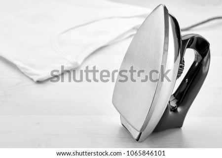 Retro iron positioned vertically and a white t-shirt on a table. Concept of ironing housework.  #1065846101