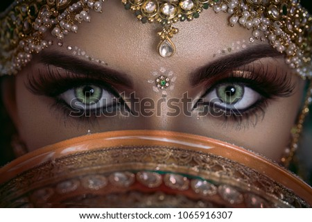 Beautiful Muslim Woman face portrait with bindis and paint.  Close up of beauty arabian or indian woman with perfect makeup and big green eyes. Royalty-Free Stock Photo #1065916307