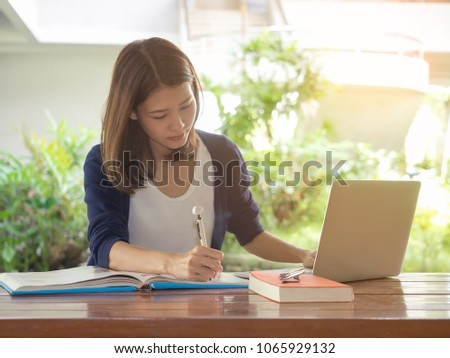 Young asian woman sitting at table doing assignments in college library. #1065929132