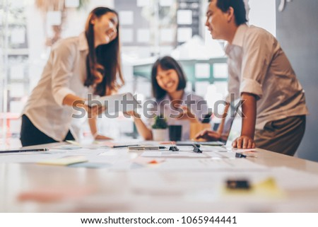 Business team working in office. The team meeting and working for project. And talking in group. On the table have laptop, tablet and paperwork. In hand hold a pen and pencil. #1065944441