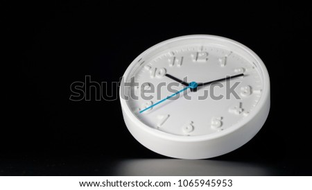 White wall clock isolated with black background. Lowkey photo concept. #1065945953