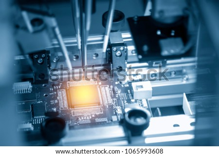 The microchip on the main board in the assembly line in the light blue scene with lighting effect, computer part manufacturing concept. #1065993608
