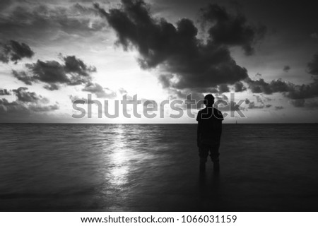 Scenery of the ocean with silhouette of a man #1066031159