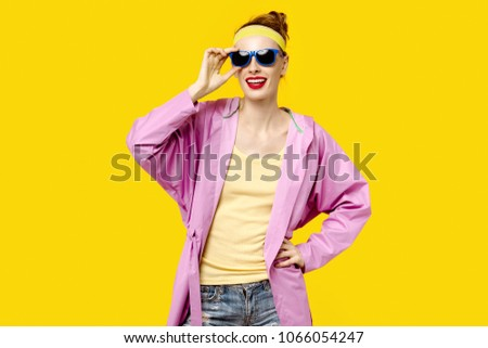 Young woman on a yellow background and pink coat and sunglasses. Colour obsession concept.  Minimalistic style. Stylish Trendy #1066054247
