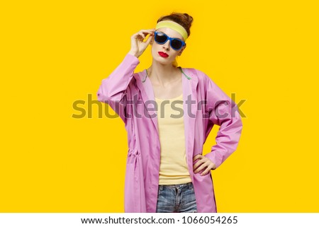 Young woman on a yellow background and pink coat and sunglasses. Colour obsession concept.  Minimalistic style. Stylish Trendy #1066054265