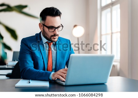 Young businessman working with laptop at modern office. #1066084298