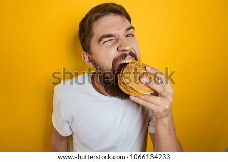man hungry eating a hamburger                               #1066134233