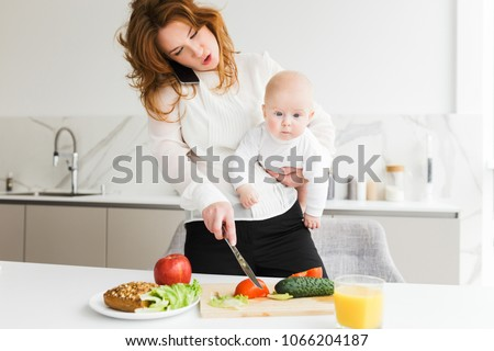 Close up photo of young mother standing and holding her little baby while talking on her cellphone and cooking on kitchen isolated #1066204187