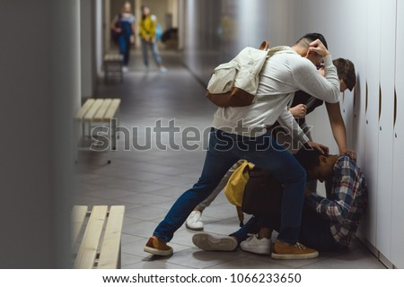 frightened african american schoolboy being bullied in school corridor Royalty-Free Stock Photo #1066233650