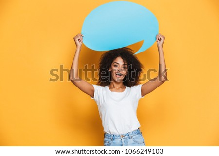 Portrait of a happy young african woman holding empty speech bubble isolated over yellow background #1066249103