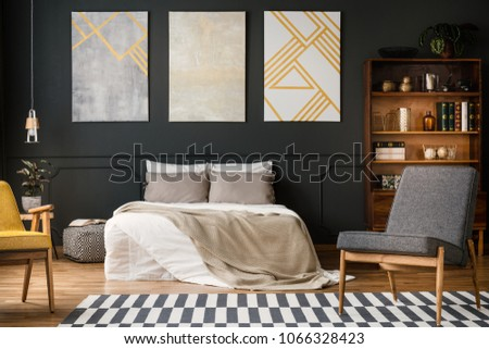Modern bedroom interior with big bed, grey and white carpet, chairs, paintings, lamp and bookcase with books and decorations #1066328423