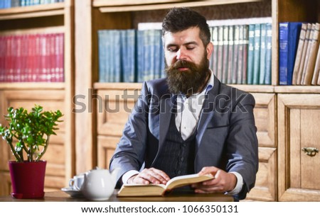 Aristocrat on thoughtful face reading book. Aristocratic lifestyle concept. Oldfashioned man near cup, teapot. Man in classic suit sits in vintage interior, library, book shelves on background. #1066350131