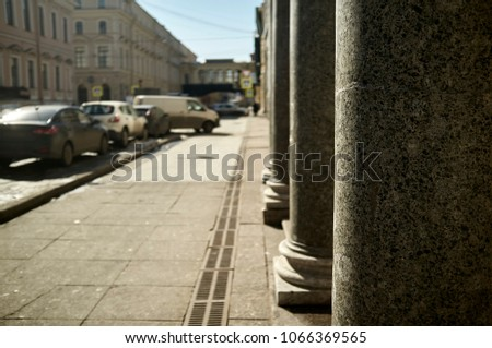 Powerful columns of an old building on the street with parked modern cars at the curb of stone slabs, sunny spring day. Close-up. #1066369565