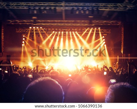 Concert hall crowded with people in front of a stage lit for the gig #1066390136