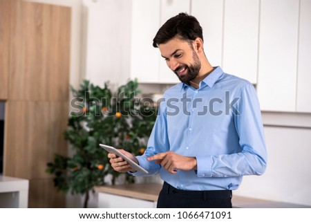 Modern user. Positive handsome businessman smiling while using his tablet #1066471091