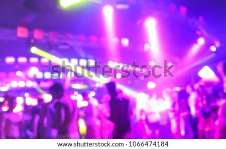 Blurred people dancing at music night festival event - Abstract defocused image background of disco club after party with laser show - Nightlife entertainment concept - Bright marsala spotlight filter