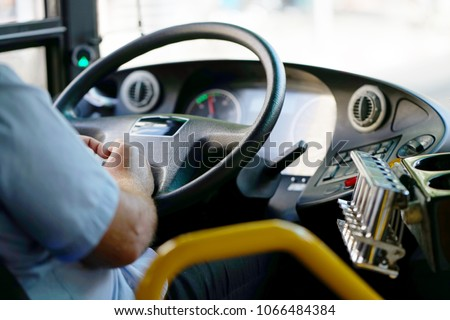 Hands of driver in a modern bus by driving.Concept - close-up of bus driver steering wheel and driving passenger bus #1066484384