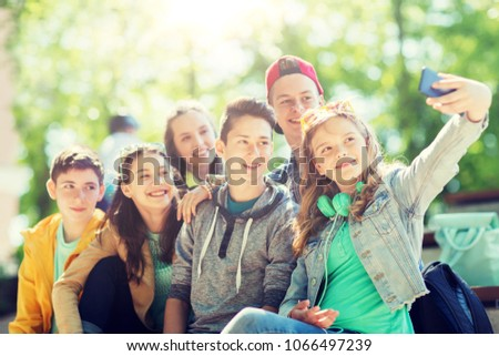 education, high school, technology and people concept - group of happy teenage students or friends taking selfie by smartphone #1066497239