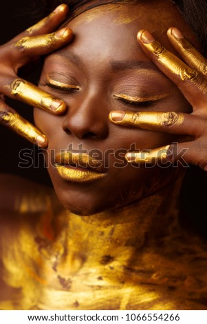 black african model covered painted with a glod paint posing for the bauty portrait, skin colored with paint Royalty-Free Stock Photo #1066554266