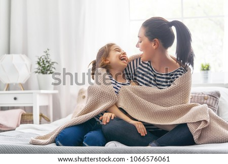 A nice girl and her mother enjoy sunny morning. Good time at home. Child wakes up from sleep. Family playing under blanket on the bed in the bedroom. Royalty-Free Stock Photo #1066576061