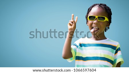 Boy in sunglasses making peace sign against blue background #1066597604