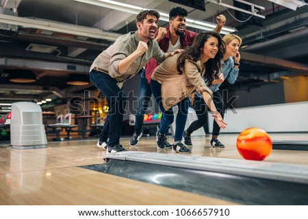Shot of an attractive brunette throwing the bowling ball while her friends are cheering